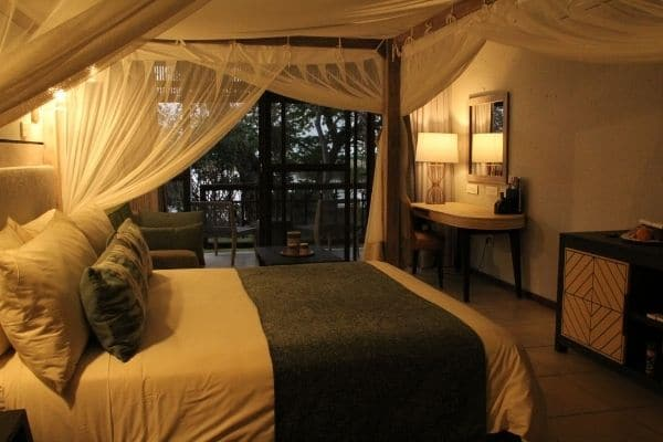 Accommodation on the Zambezi River - picture shows cosy room with lamps on, there is a double bed in the room and in background balcony overlooking the Zambezi River