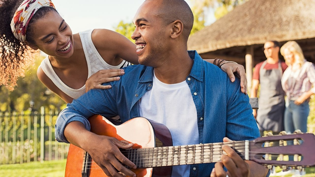 Young musician smiling whilst he is seating playing guitar with female friend slightly behind him with her arms around his shoulders