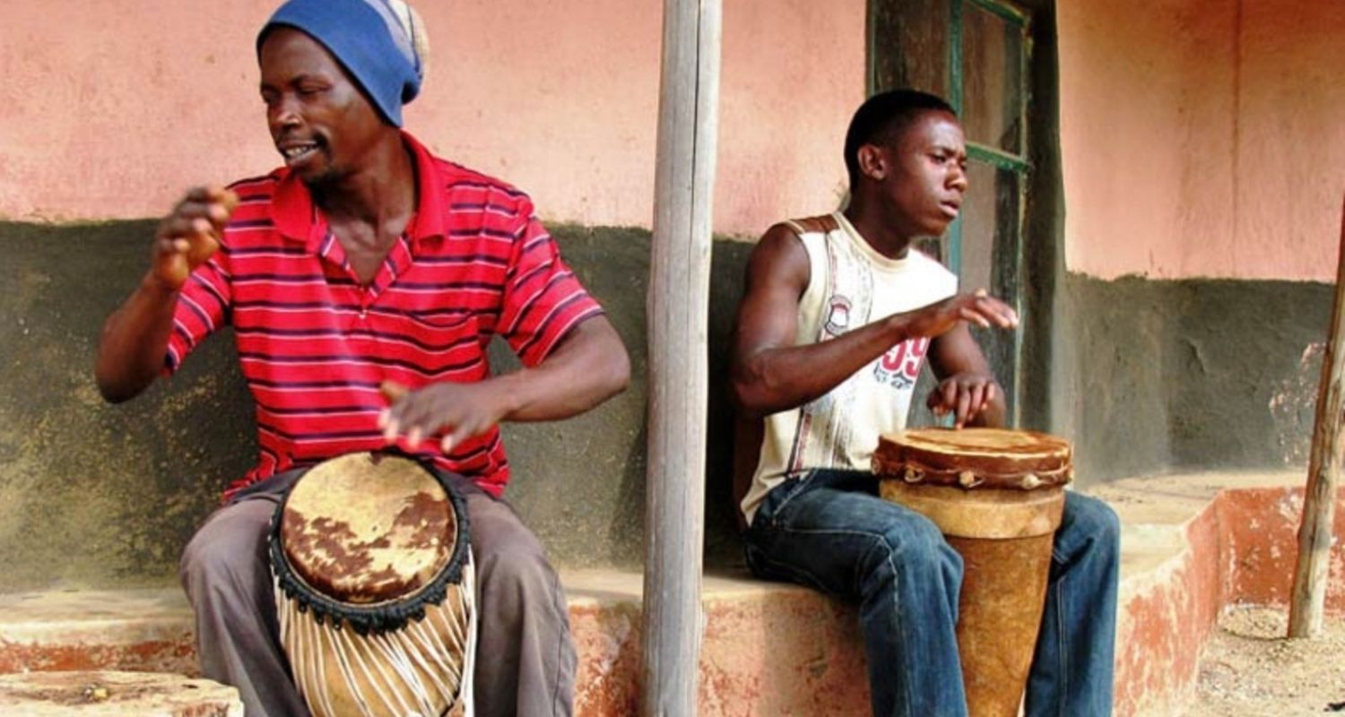 Two local African men playing the drums