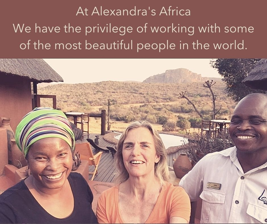 Alexandra standing with Eco-Lodge Managers with lodge and mountains in background