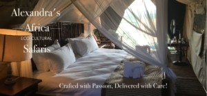 Inside one of our Alexandra's Africa Luxury Tents - on our Classic Safari - big double bed covered with mosquito net with soft lamp in foreground lighting up the bed