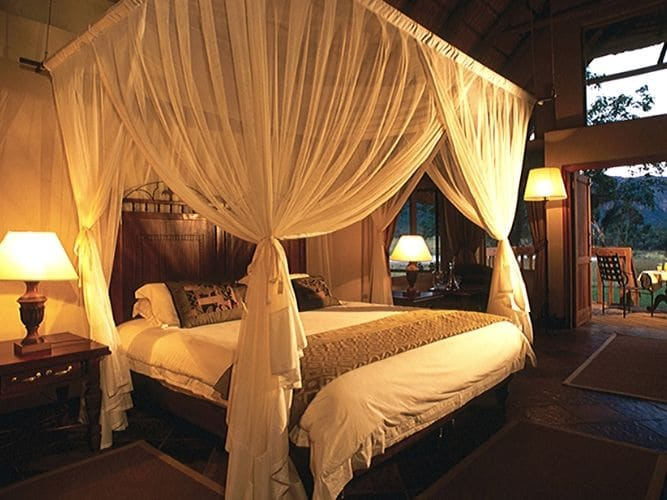 Picture of 4 poster double bed with mosquito net inside first lodge - bed is made up with crisp white linen and there are lamps either side of the bed creating a lovely hue