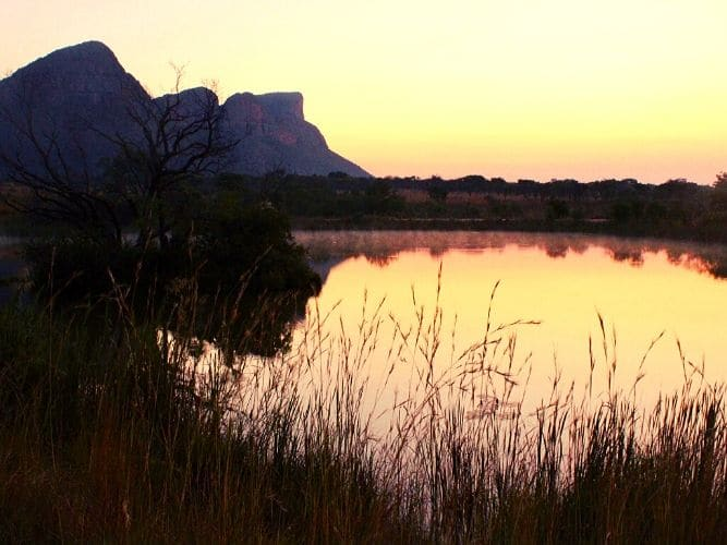 Sunset over a lake with mountains in the background - game drive view on our Alexandra's Africa Getaway Safari