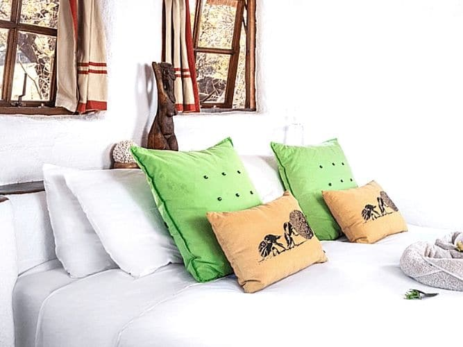 Close up of cosy double bed with white linen and scatter cusions inside eco-village mudhut accommodation