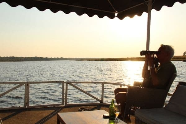 A man enjoys a sundowner on an evening game spotting cruise whilst looking out across the river through binoculars