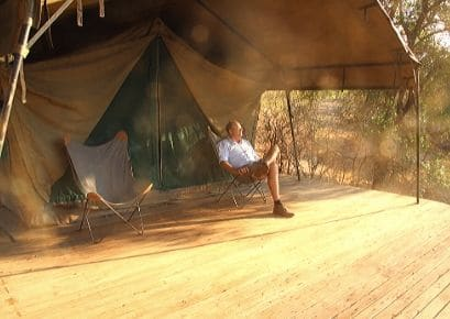 Alexandra's Africa guest sitting relaxed and peacefully outside his tent looking out into distance