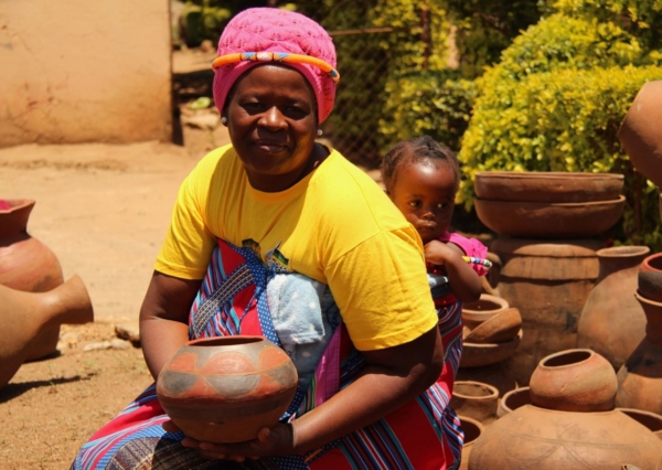 Florah Randela with baby on her back - showing off one of her beautiful pots