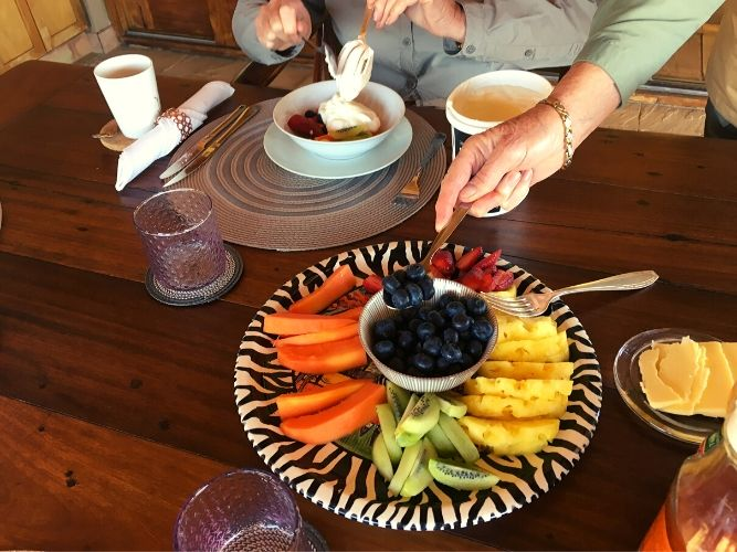 Breakfast plate of fresh fruit with guest taking a helping