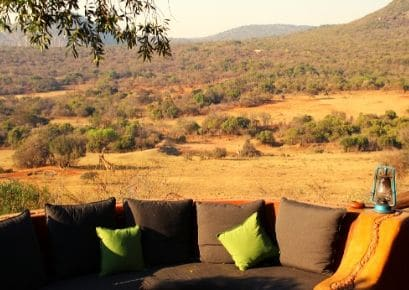 View from Alexandra's Africa game lodge overlooking valley. Chairs with cushions & oil lamp in foreground.