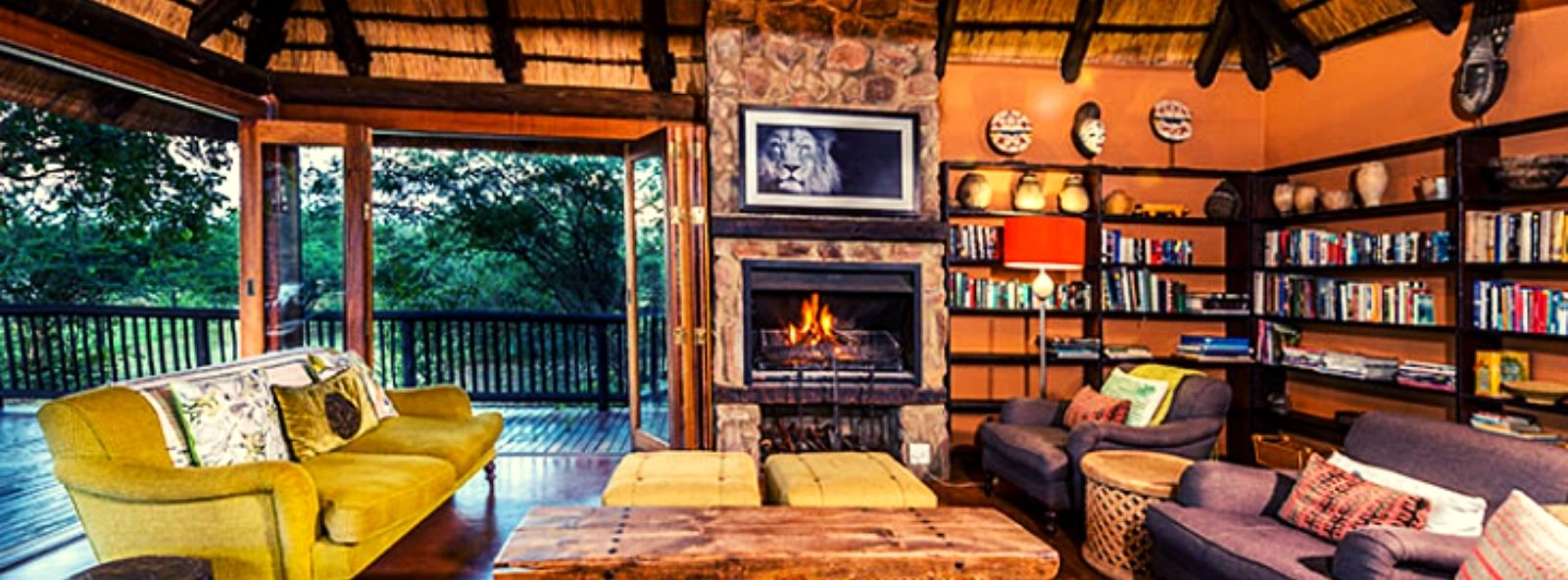 Getaway 8 Safari Accommodation Sitting Room with cosy sofas coffee table bookcase and log fire in background