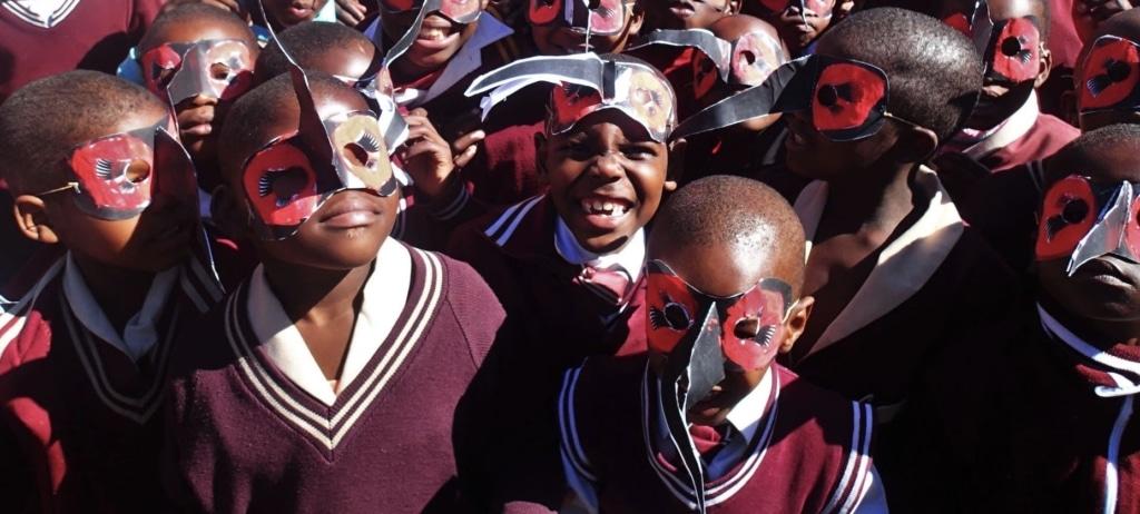 Group of African School Children wearing Ground Hornbill Masks