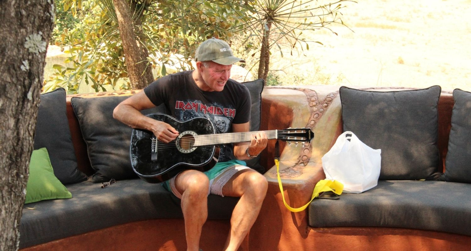 Man sitting on an outdoor seating area in the sun playing an acoustic guitar