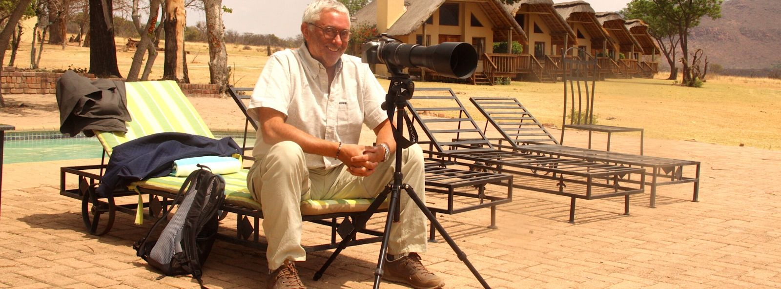 Man sitting with camera outside lodges