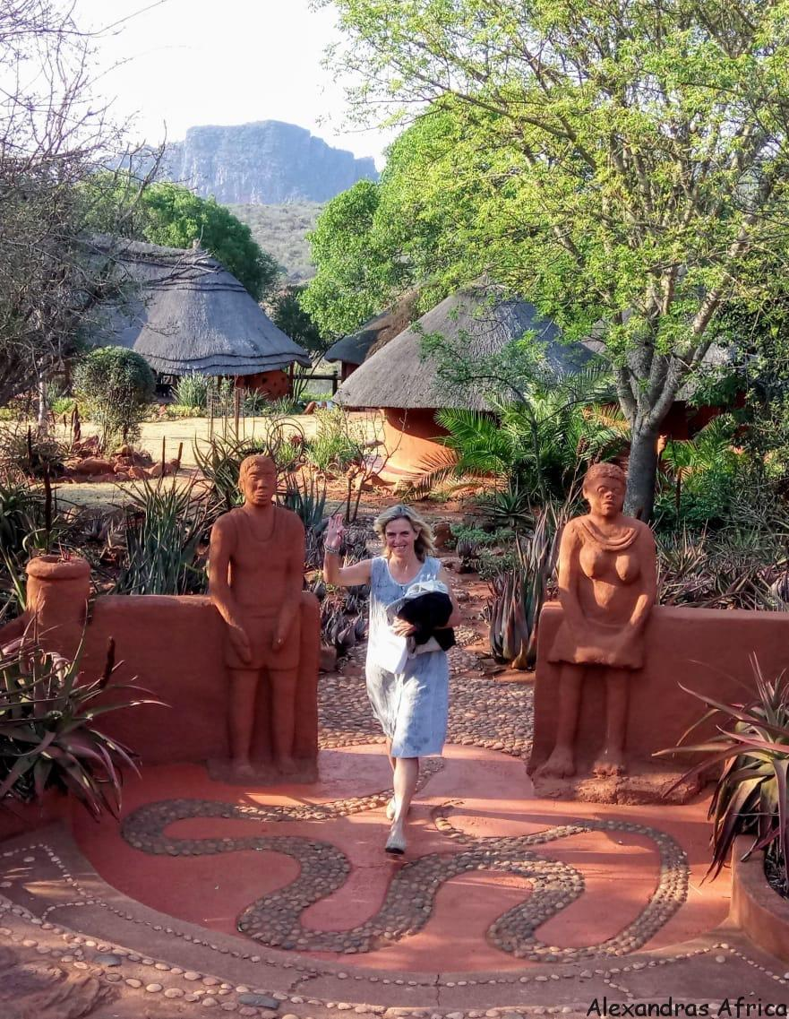 Alexandra walking towards the camera and waving with our Alexandra's Africa Venda Village Eco Lodge in background