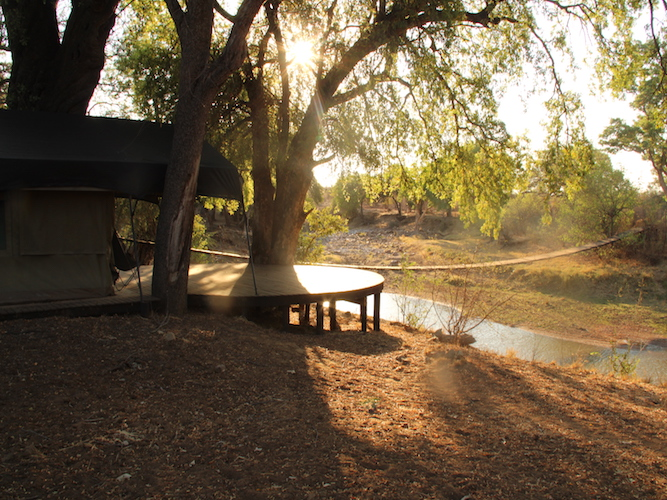 Picture of the front of luxury tent showing expansive decking area and the view from the tent over the Limpopo River