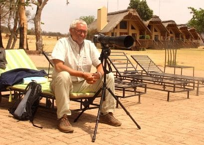 Man sitting with camera outside the Alexandra's Africa Safari lodges