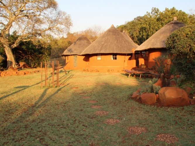 Picture of a cluster of Venda Mud Huts - lit up by the setting sun. This is the eco-lodge used by Alexandra's Africa on all Safaris