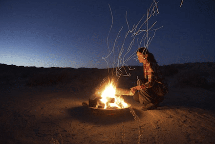 Woman kneeling next to a campfire in Africa under open skies