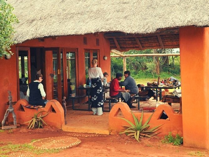 Alexandras Africa Retreat Group relaxing at front of lodge in patio area under thatched roof