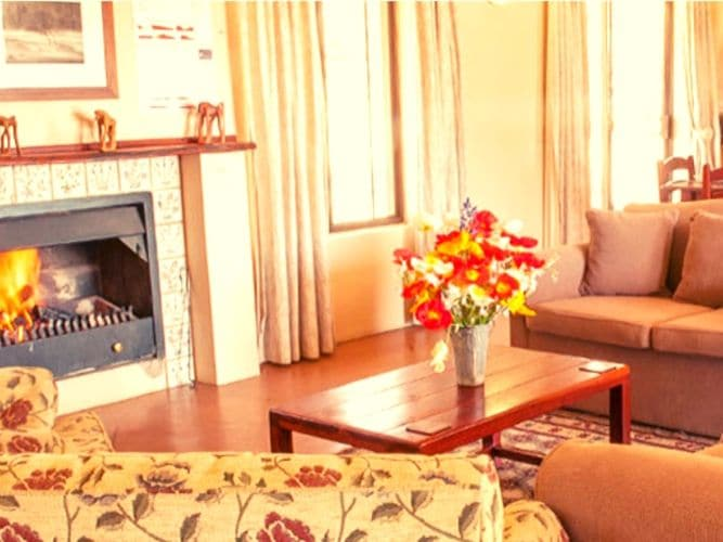 Living room - with cosy fire and lovely fresh flowers on the table - of our main retreat farmhouse cottage base