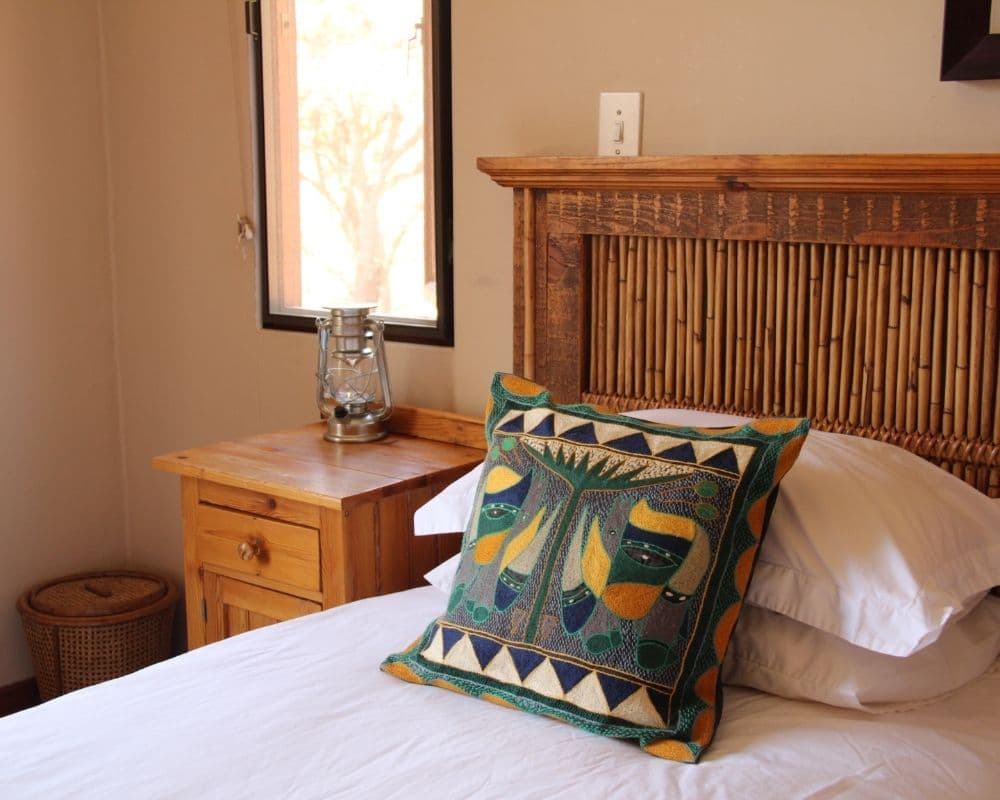 Bed with wooden frame and decorative cushion