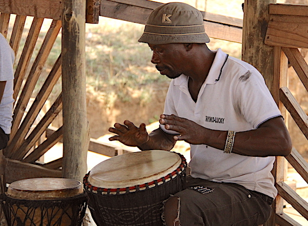 Limpopo Musician Lucky Ntimani seated playing an African drum in his studio