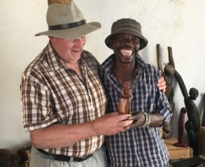 Lucky Ntimani standing with Alexandras Africa guest with arm around Lucky in Lucky's Gallery of wood carvings