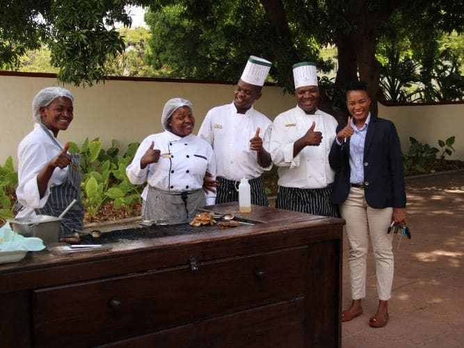 Kitchen team of 6 chefs and manager at Victoria Falls looking at camera and smiling all giving a thumbs up