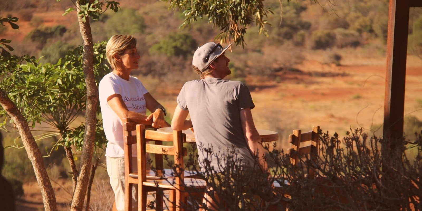 Alexandra's Africa guest chatting to a member of the team on the balcony of the lodge overlooking the valley below