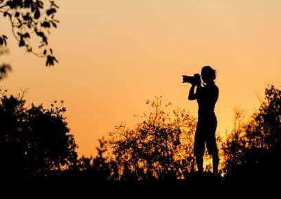 Alexandra's Africa guest taking a picture with SLR camera with long lens. Active stance - with lovely amber Sunset background