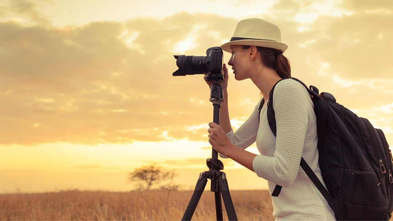 Female photographer in Africa in open savannah grasslands with sunset behind looking through viewfinder of camera on tripod
