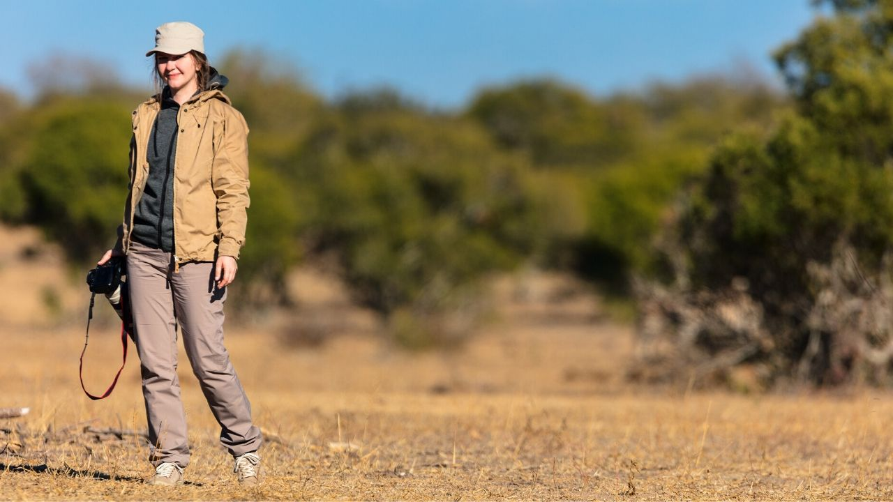 Female photographer in Africa walking in the bush camera in hand looking relaxed at camera - scenery behind is out of focus