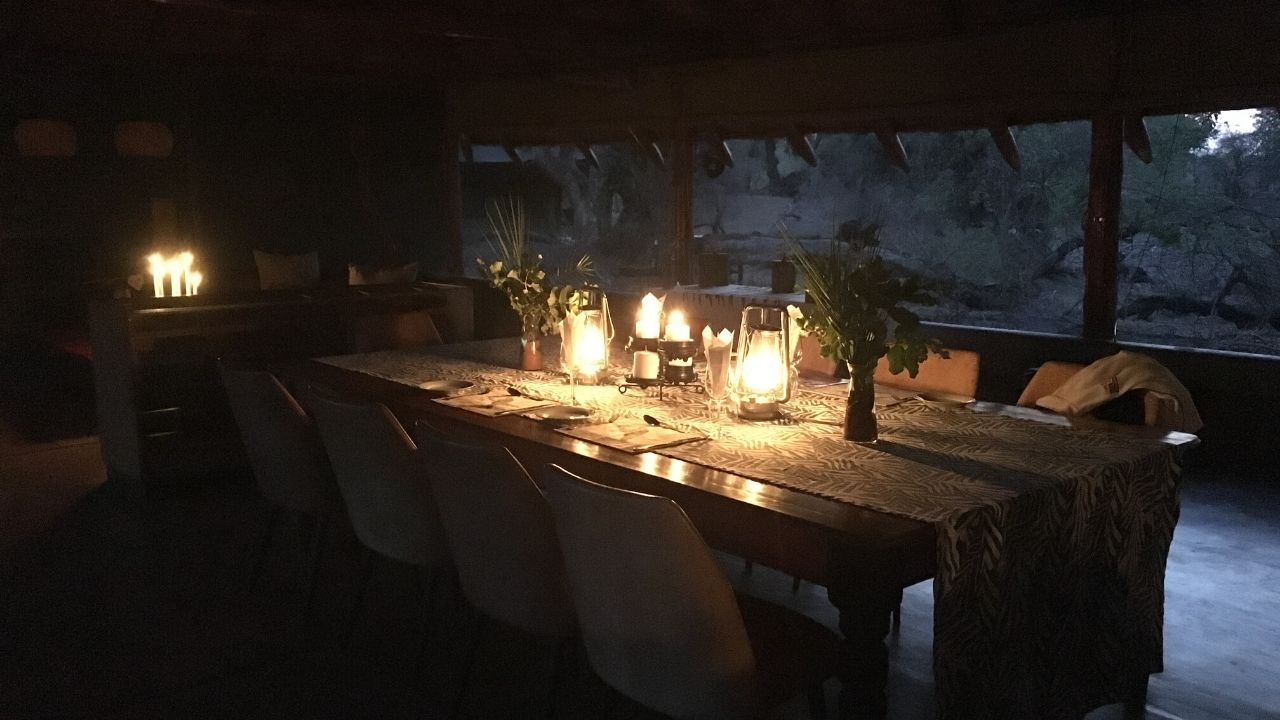 Picture of a table set for dinner full lit by candles with open views out onto the Limpopo River in the distance