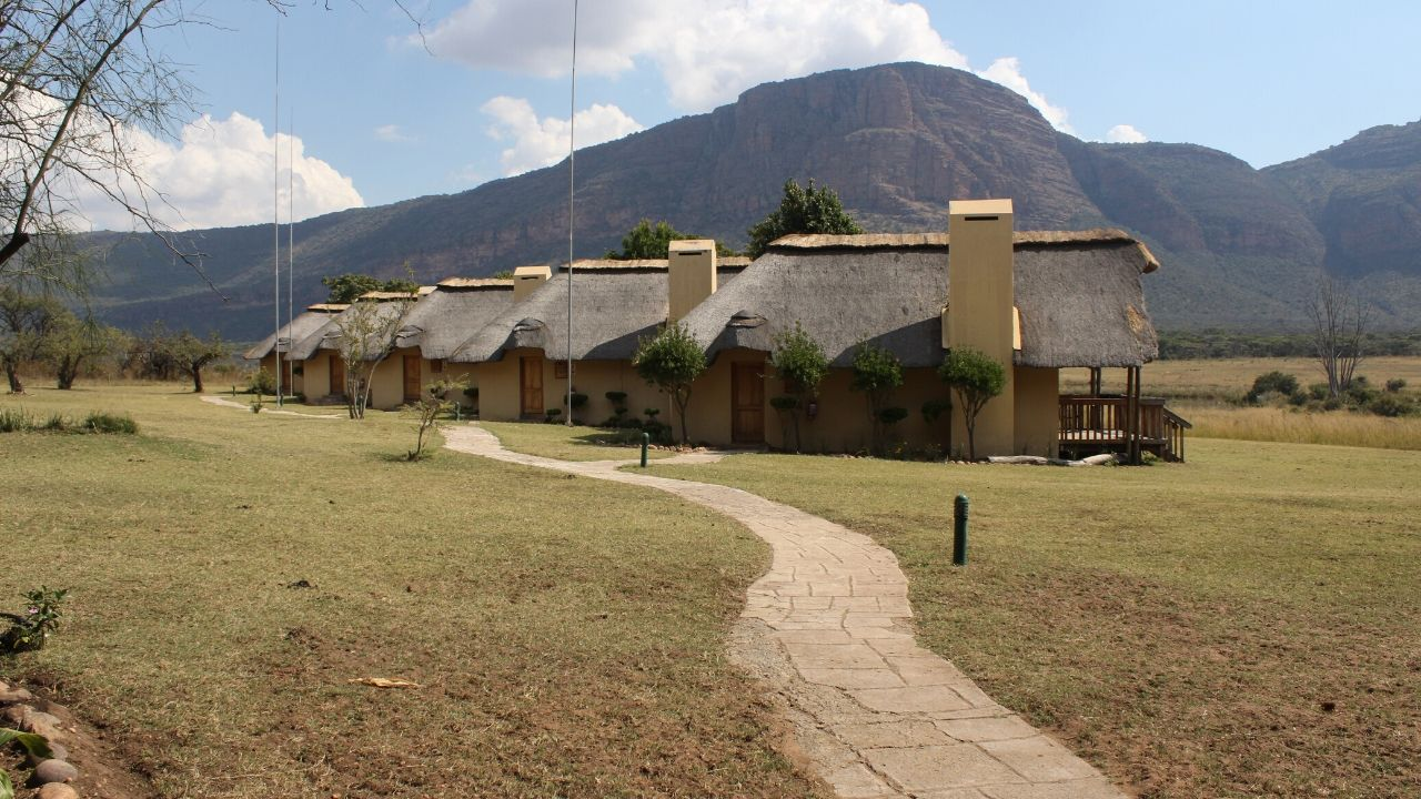 A curved path leading to a row of thatched Safari Guest Cottages with mountains in background
