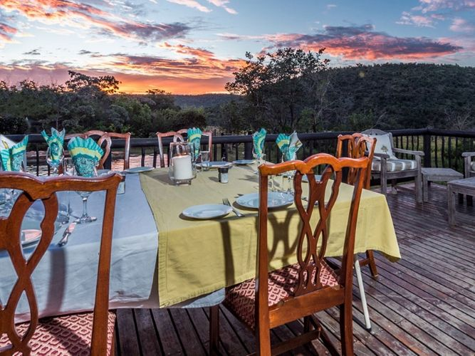 Tables set for dinner on a wooden terrace in Africa looking out of savannah at sunset