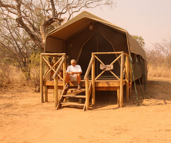 Alexandra's Africa guest sitting on the steps of his furnished tented accommodation - in South Africa