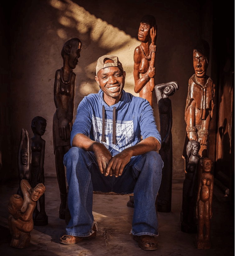 David Murathi Ribola Art Route Artist sitting and smiling facing camera with his sculptures behind him