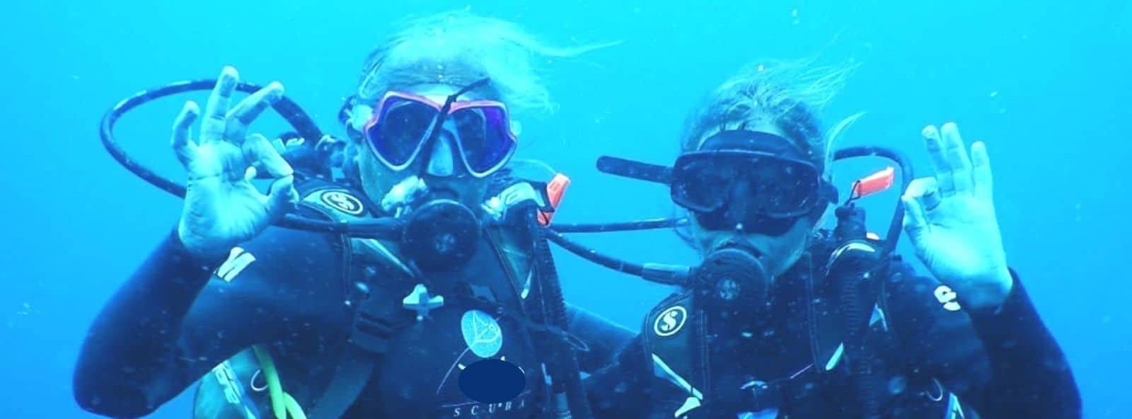 Scuba Diving Buddies - Close up of faces of two Women under water Scuba Diving - showing the universal all OK sign