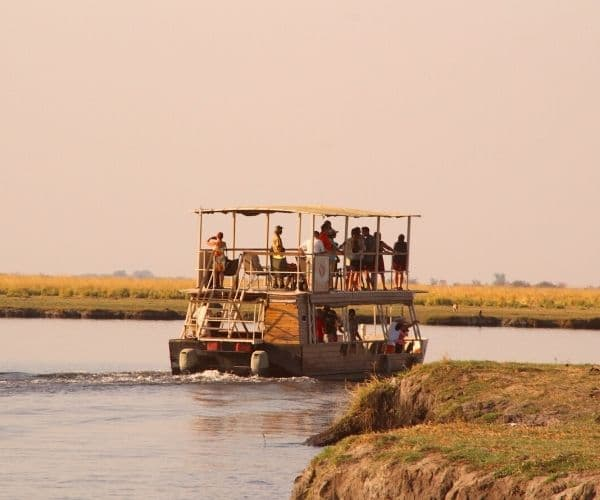 An open sided double decker boat with guests on board for a sunset cruise on the Chobe River in Botswana