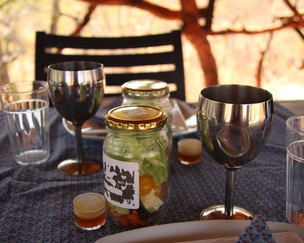 wine glasses and jar of food set on a table