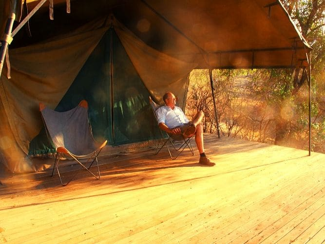 Guest sitting looking relaxed and enjoying the view outside tent on Alexandra's Africa Explorer Safari