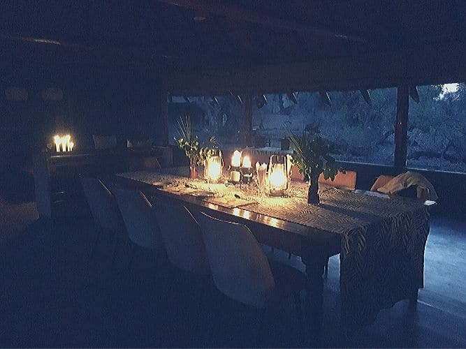 Dining area at Limpopo River lodge - dining table covered with candles and views out over Limpopo River