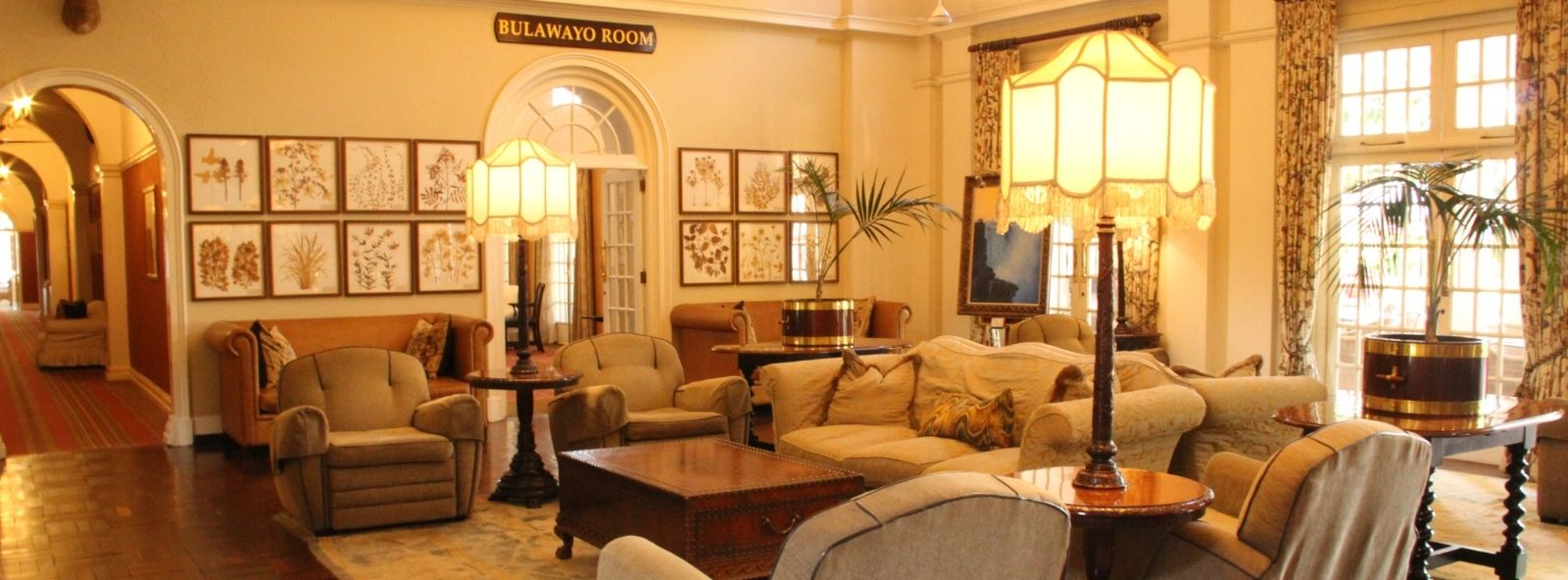 The magnificent sitting room of the Victoria Falls Hotel - A room tastefully furnished with armchairs, lamps, piano and polished side tables and plants - colonial style