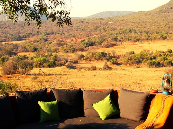 View over the valley from our Alexandra' s Africa Safari Venda eco-lodge. Oil lamp and comfy chairs and cushions in foreground - valley and mountains in the background.