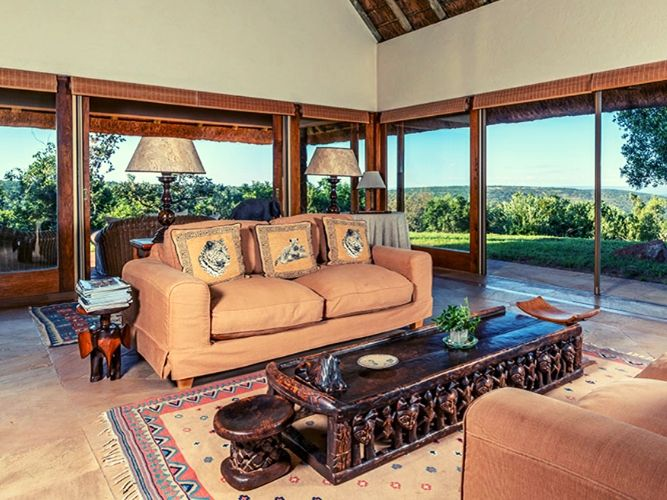 Inside final lodge view of the comfortably furnished drawing room onto terrace and open bushveld