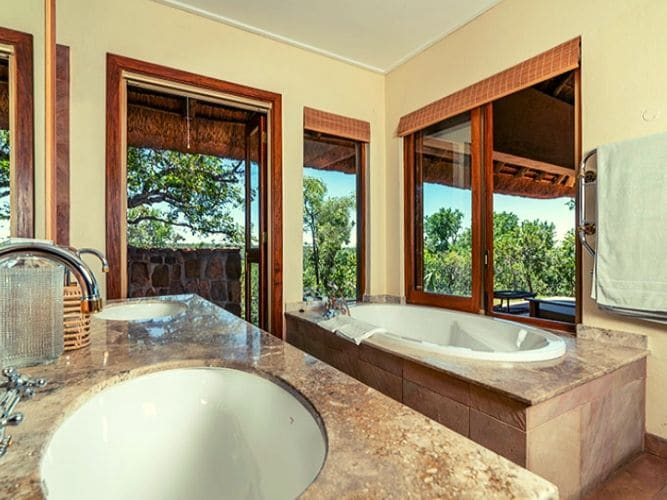 Inside bathroom of one of guest rooms - handbasin in foreground and oval bath in background - views out over the surrounding bushveld