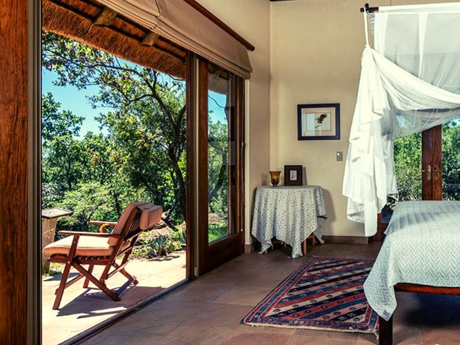 View from the inside of one of the lodge bedrooms from inside looking out to terrace and views out over bushveld