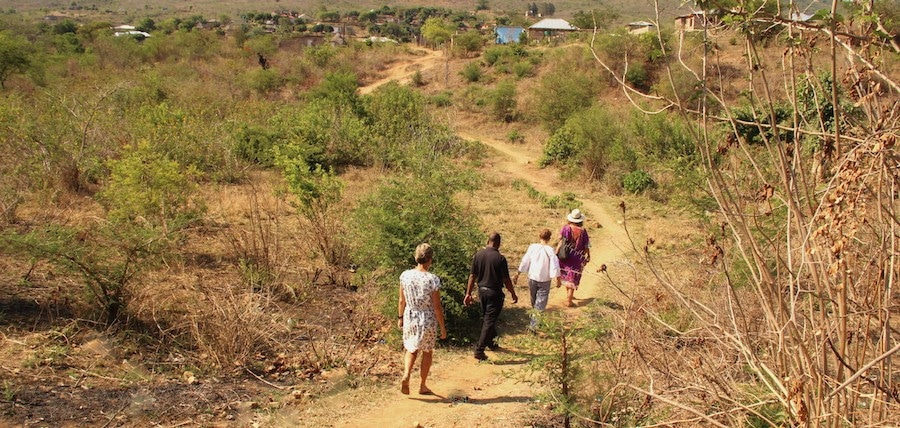 Alexandra's Africa guests walking on dusty path to African Village