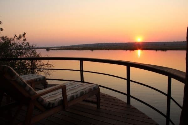 Looking out over the Chobe River from the balcony of one of our Tailored Safari Hotels with the sun setting in the background