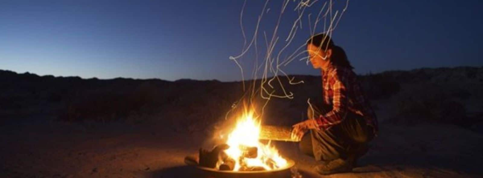 Woman putting a log on campfire at sunset - vast early night dark blue skies in background